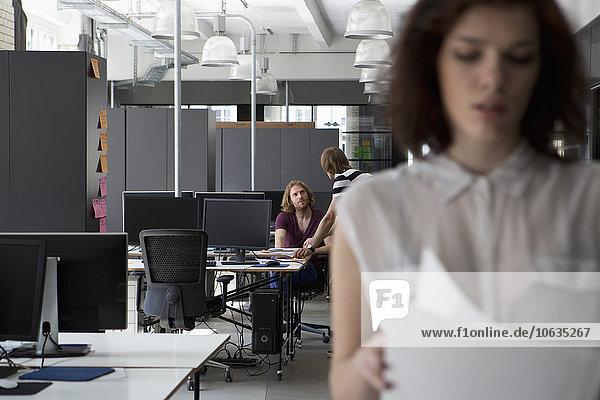 Kollegen diskutieren im Büro  Frau mit Dokumenten im Vordergrund