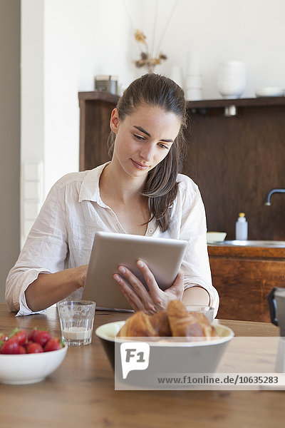 Young woman sitting at dining table  using digital tablet
