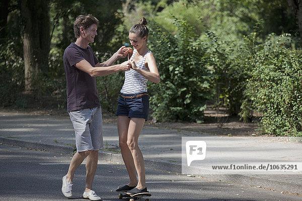 Junger Mann lehrt Frau das Skaten