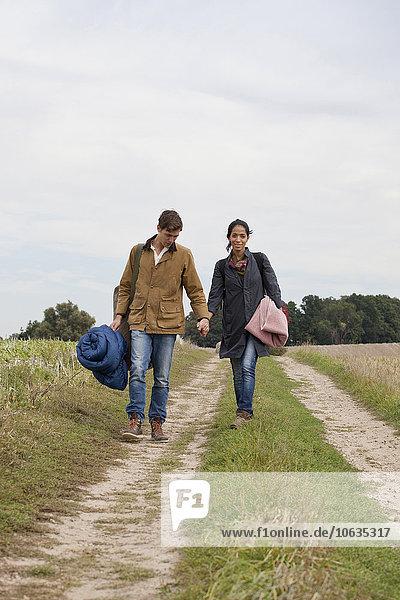 Junges Paar mit Campingaccessoires beim Spaziergang durch die Schotterpiste