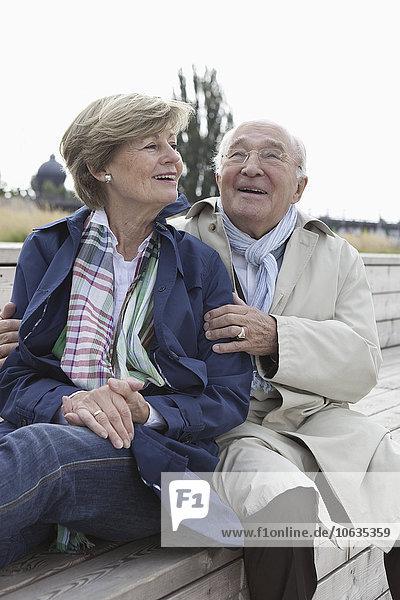Paar auf einer Treppe im Park sitzend