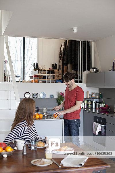 Frau sitzt am Esstisch  während der Mann das Frühstück in der Küche zubereitet.