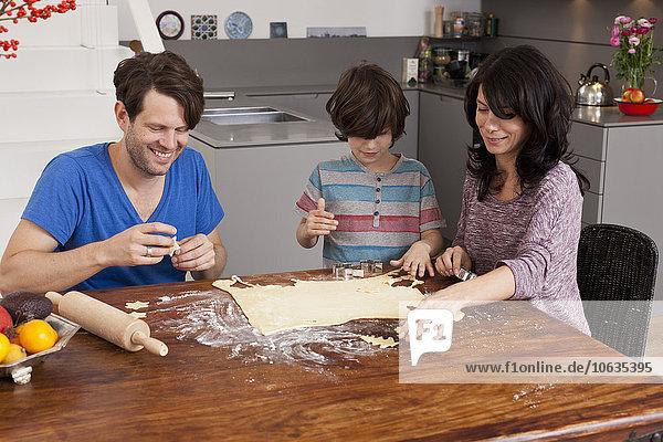 Familie macht Weihnachtsgebäck am Esstisch
