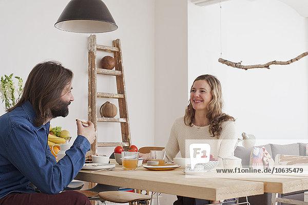 Lächelndes Paar beim Frühstück zu Hause