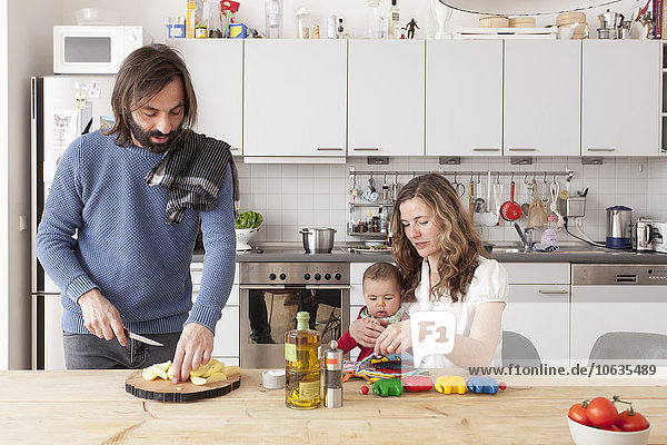 Father chopping vegetables with mother and baby girl playing in kitchen