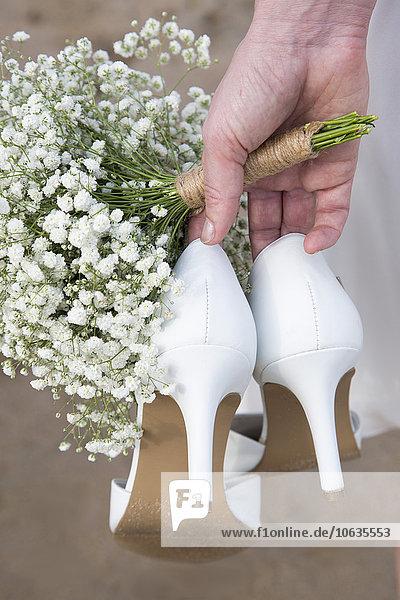 Beschnittenes Bild der Braut mit hohen Absätzen und Blumen