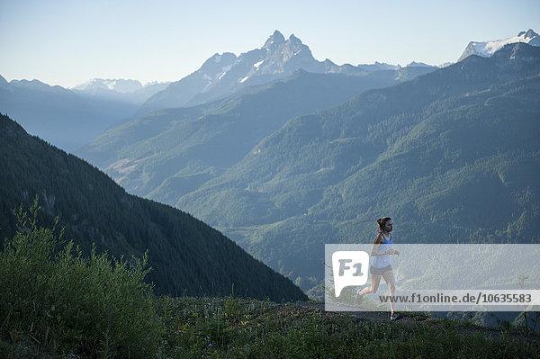 Frau joggt auf dem Weg in den Bergen Frau joggt auf dem Weg in den Bergen