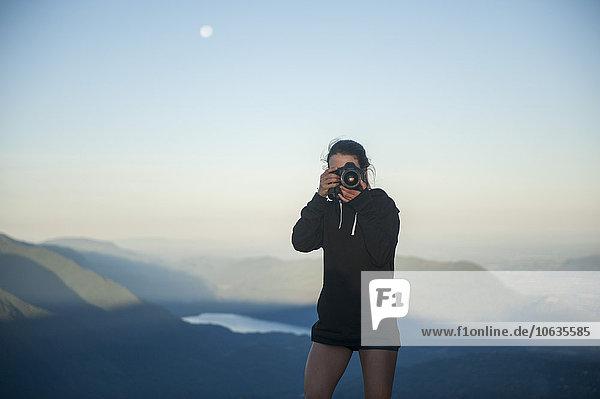 Mittlere erwachsene Frau fotografiert mit Bergen im Hintergrund Mittlere erwachsene Frau fotografiert mit Bergen im Hintergrund