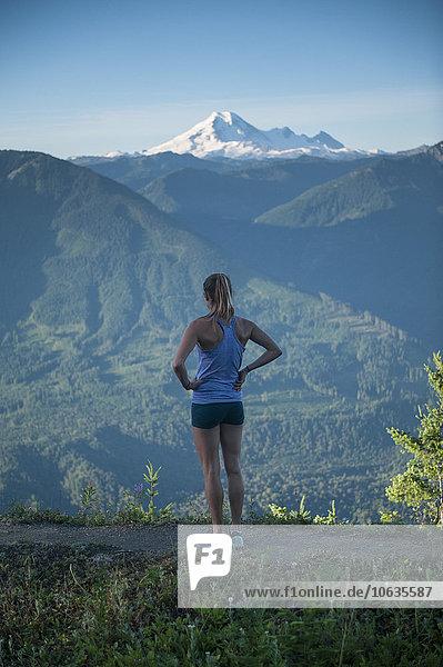 Durchgehende Rückansicht der sportlichen Frau mit Blick auf die Berge Durchgehende Rückansicht der sportlichen Frau mit Blick auf die Berge