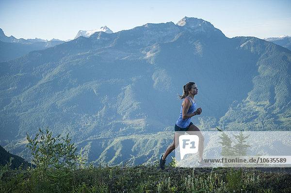 Seitenansicht der sportlichen Frau beim Joggen auf dem Bergweg Seitenansicht der sportlichen Frau beim Joggen auf dem Bergweg