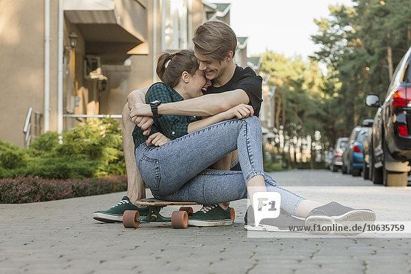 Glückliches junges Paar  das sich auf dem Skateboard im Freien umarmt.