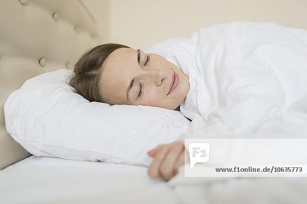 Lächelnde Frau schläft zu Hause im Bett
