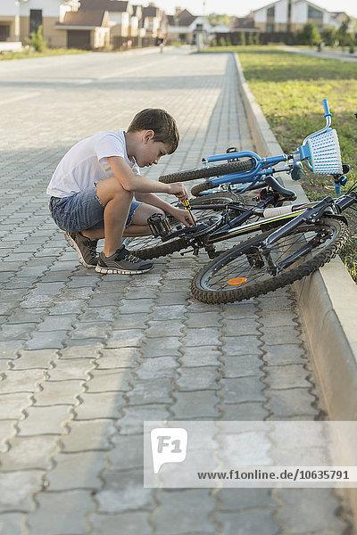 Seitenansicht des Jungen bei der Fahrradreparatur auf dem Fußweg