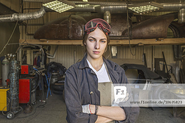 Portrait of confident female mechanic with arms crossed at garage
