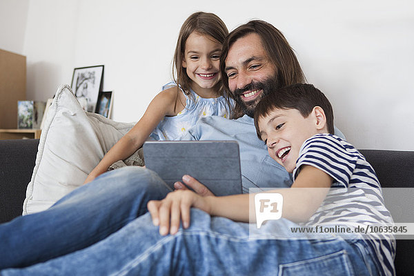 Happy father with children using digital tablet on sofa at home