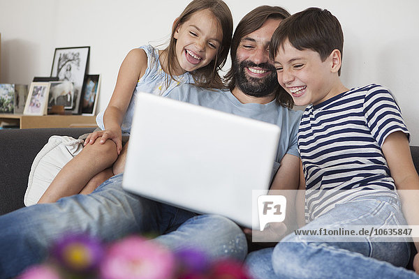 Cheerful father with children using laptop on sofa at home