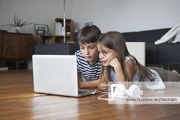 Siblings using laptop while lying on hardwood floor at home