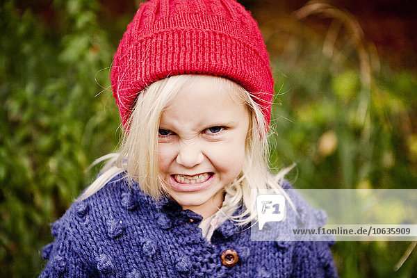 Portrait of playful girl making face in forest