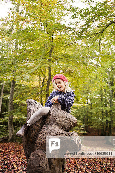 Happy girl sitting on wooden sculpture in forest