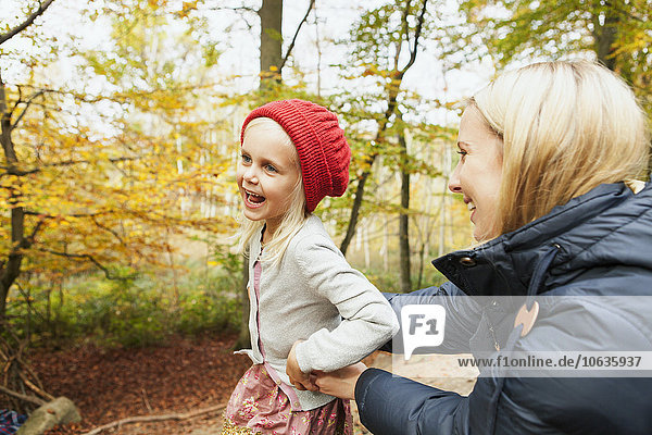 Happy mother and daughter in forest