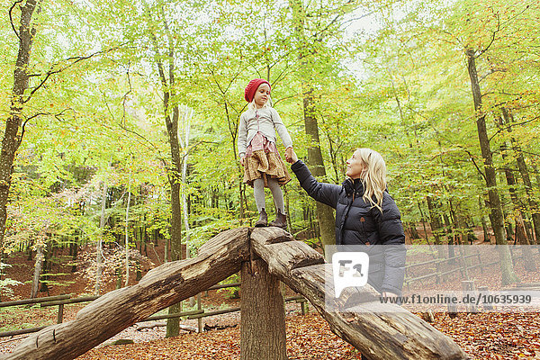 Mother looking at girl standing on wooden structure in forest