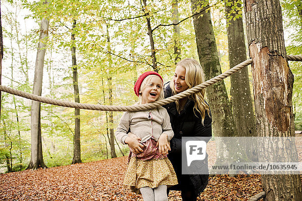 Smiling mother assisting girl balancing on rope in forest