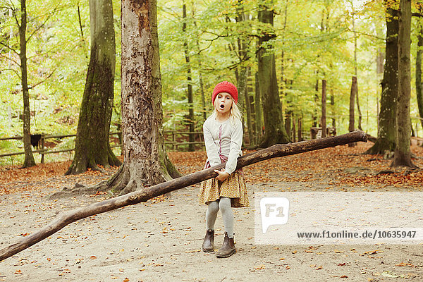 Girl carrying log while standing in forest