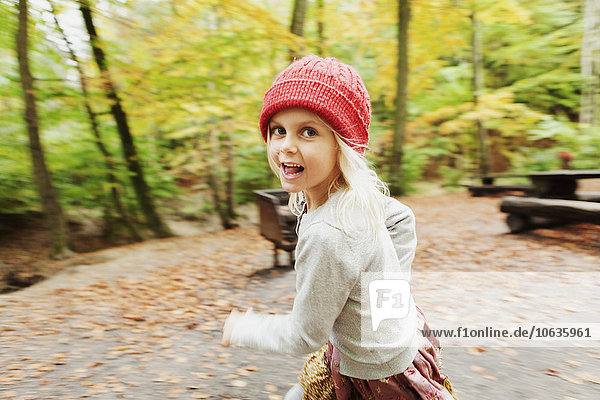 Portrait of happy girl running in forest