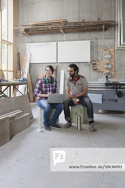 Volle Länge der glücklichen Schreiner mit Laptop in der Werkstatt