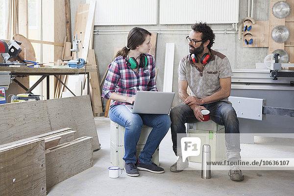Volle Länge der mittleren erwachsenen Schreiner  die während der Benutzung des Laptops in der Werkstatt diskutieren.