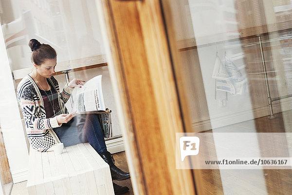 sitzend junge Frau junge Frauen Laden Kaffee Zeitung vorlesen