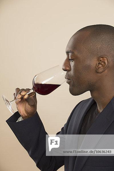 Gut gekleideter Mann bei der Verkostung von Rotwein vor farbigem Hintergrund