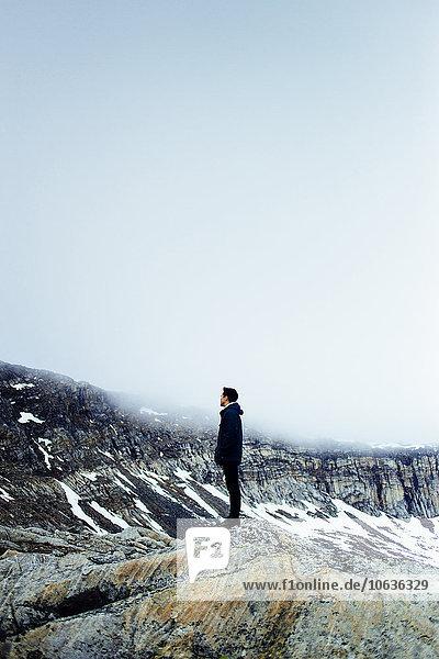 stehend Berg Winter Mann Felsen Ansicht jung Länge Seitenansicht voll
