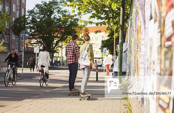 Rear view of couple skateboarding on sidewalk