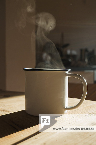 A steaming hot drink in a mug with sunlight  close-up