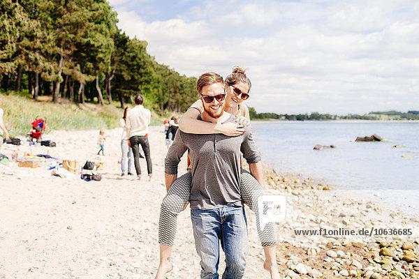 Mann Freundin geben Strand fahren huckepack mitfahren