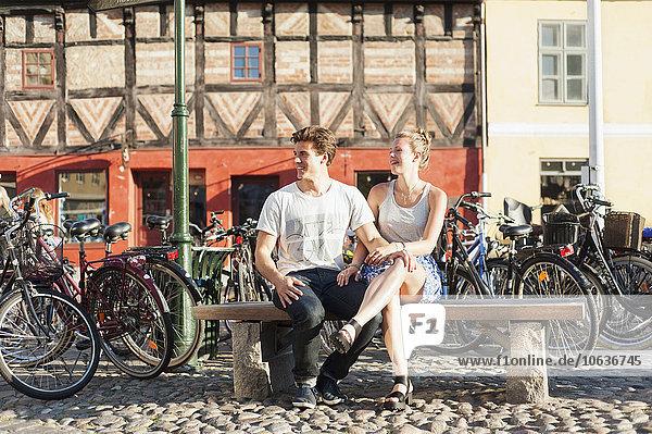 sitzend lächeln Sommer Großstadt parken Sitzbank Bank jung Länge voll