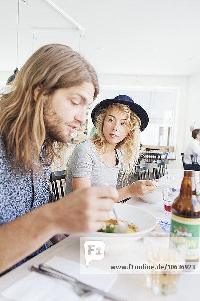 Woman looking at man while having food at restaurant table