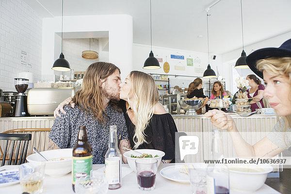 sitzend küssen Restaurant jung Tisch