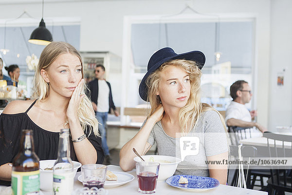 Thoughtful women looking away while sitting at restaurant table