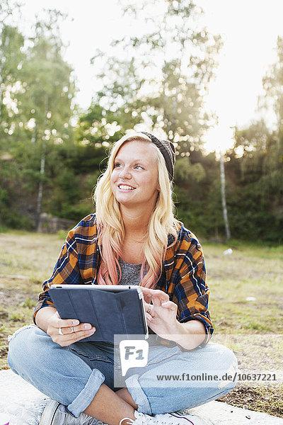 sitzend Frau lächeln Decke Picknick halten Feld Tablet PC