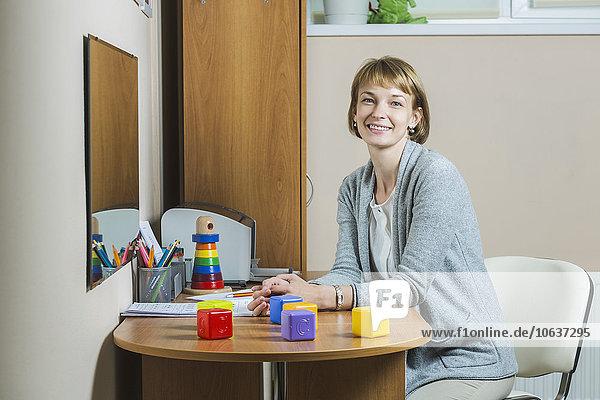 Portrait of beautiful teacher sitting on chair at school