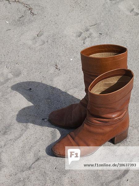 Hochwinkelansicht von Lederstiefeln auf Sand