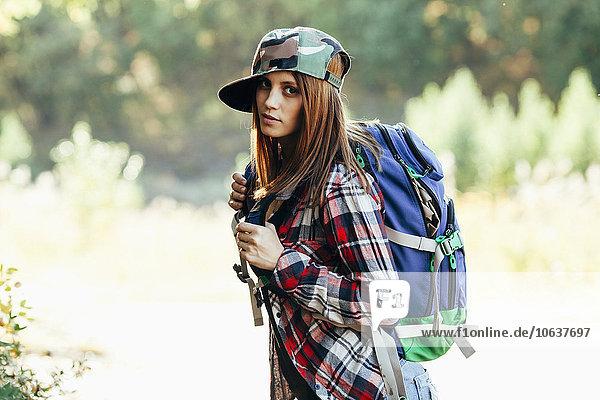 Porträt der modischen jungen Frau beim Wandern im Wald
