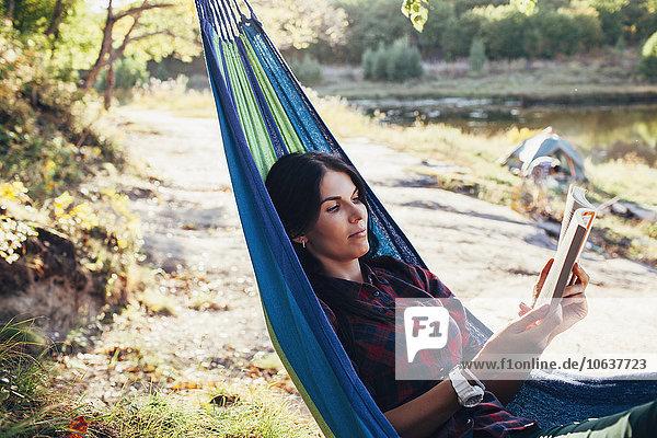 Junge Frau beim Lesen eines Buches auf der Hängematte im Wald