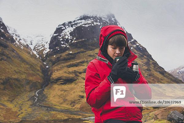 Frau trinkt im Winter Kaffee gegen den Berg