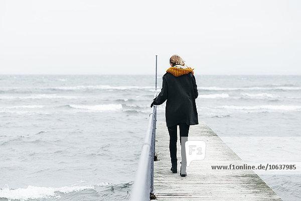 Frau gehen über Meer Kai Rückansicht Ansicht Länge voll