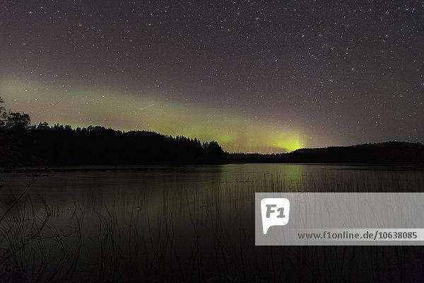 Idyllischer Blick auf Aurora Borealis am See bei Nacht