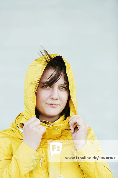 Portrait of young woman in raincoat