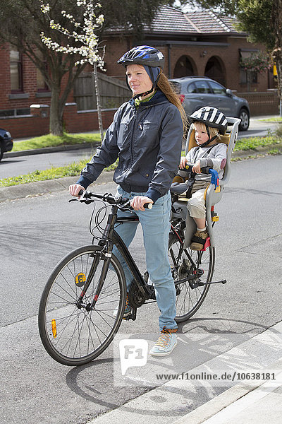 Mother and son on bicycle at city street